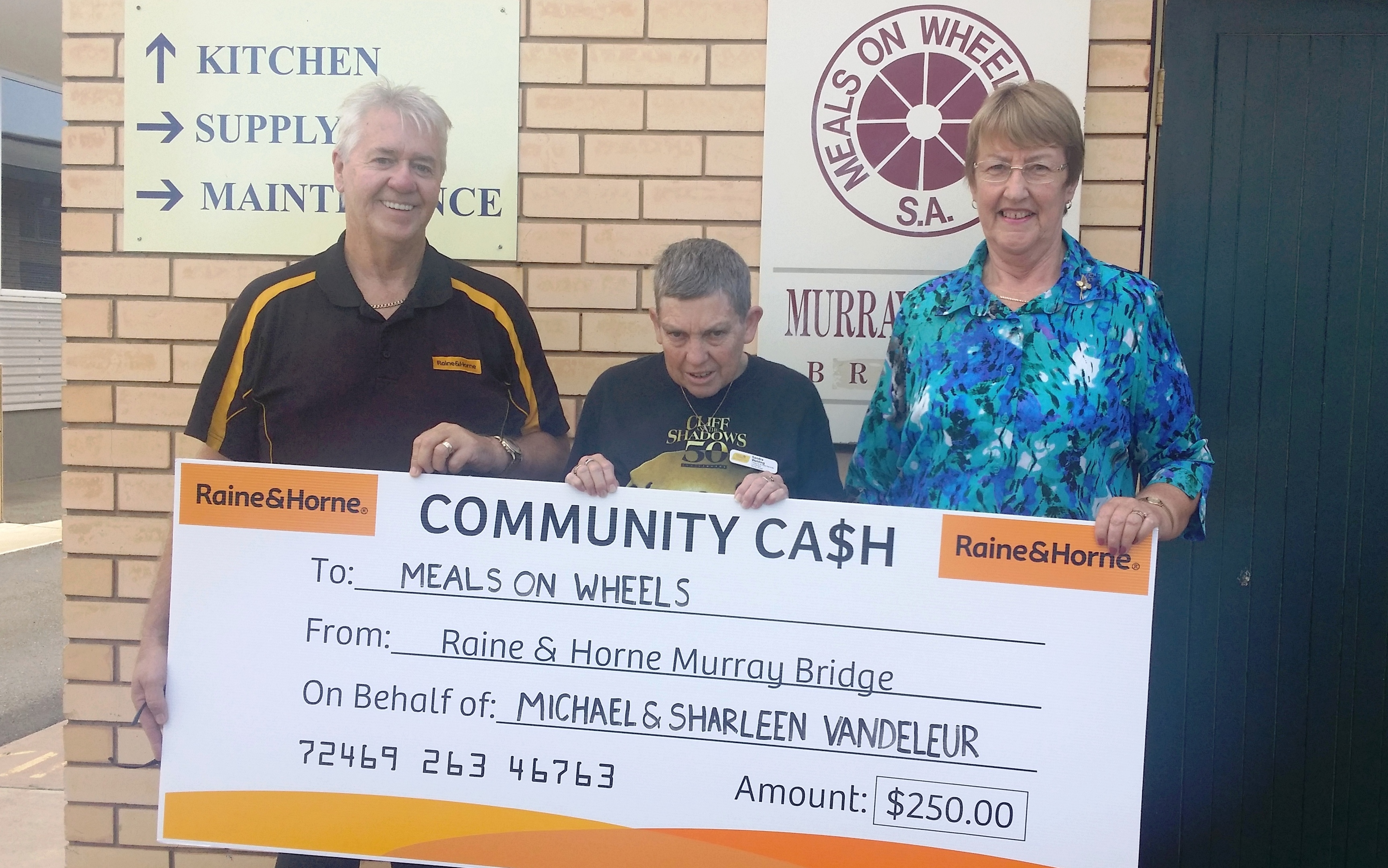 Geoff Muir of Raine and Horne Murray lands donating a cheque to Meals on Wheels